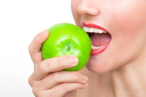 Woman bites in green apple stock photo