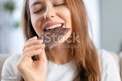 istock Woman biting a chocolate bar 1212386005