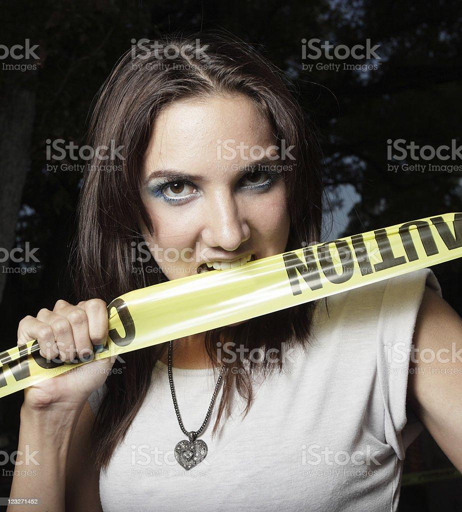 Woman biting caution tape stock photo