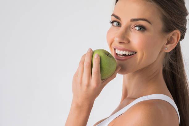 Woman biting green apple stock photo