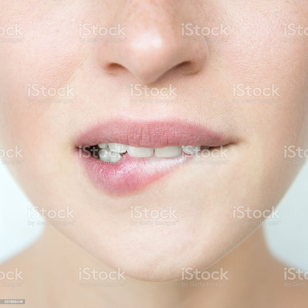 Woman biting her Lip stock photo