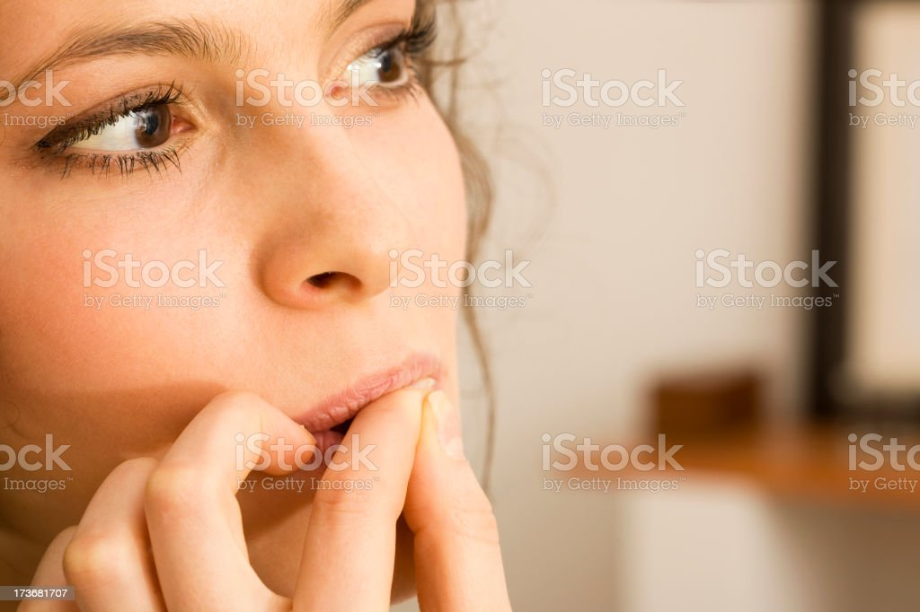 Woman biting nails stock photo