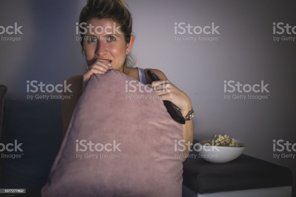 Woman biting pillow because of anticipation while watching movie stock photo