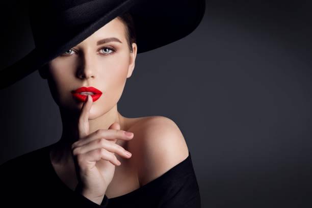 Woman Black Hat, Elegant Fashion Model Beauty Portrait, Finger on Lips Silent Gesture stock photo