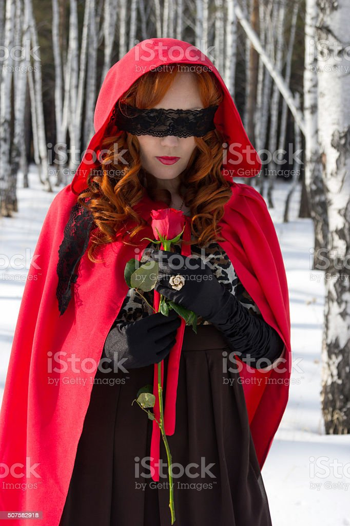 woman blindfolded and holding a rose. Surrealism stock photo