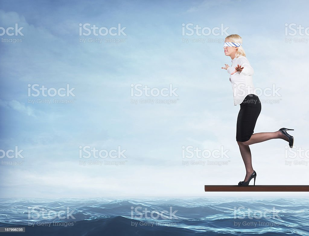 Woman blindfolded walking on a board over the sea stock photo