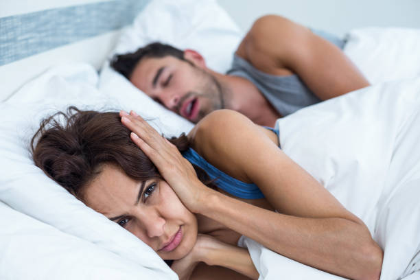 Woman blocking ears with hands while man snoring on bed stock photo