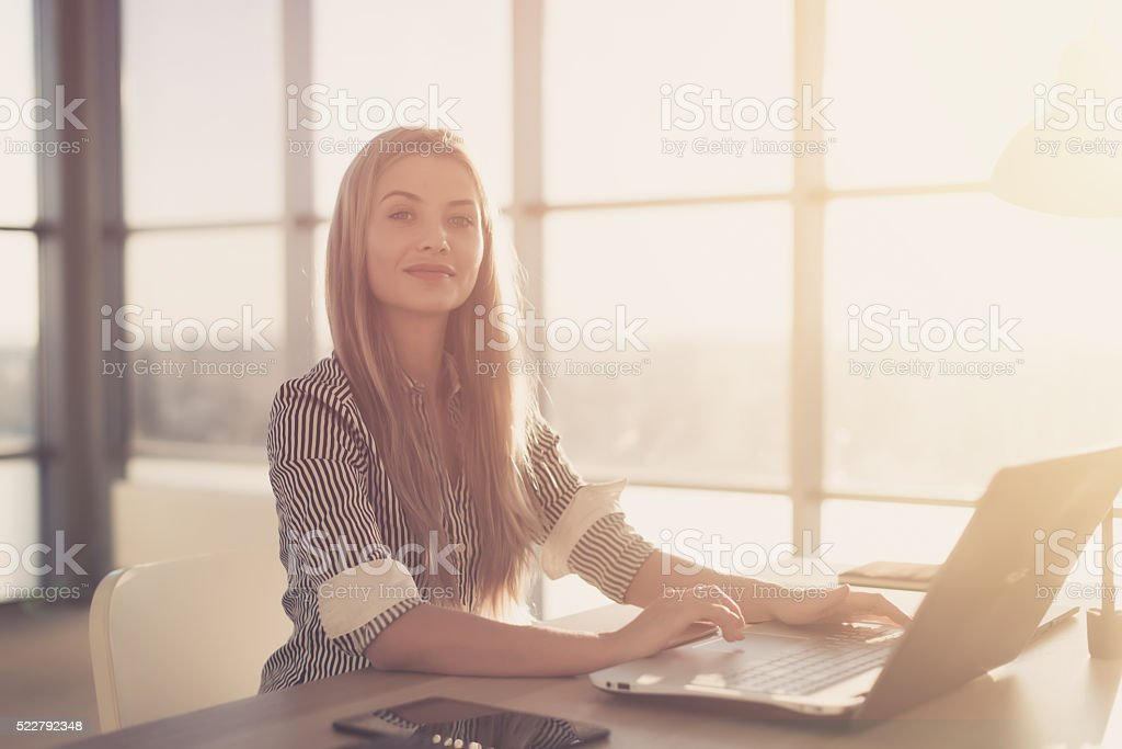 Woman blogging in spacious office using computer on her workplace stock photo