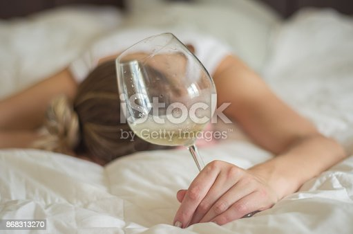 istock Woman, blond hair, fainted in bed after drinking 868313270