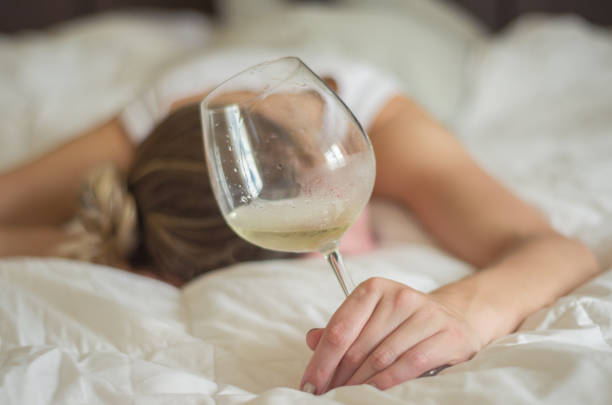 Woman, blond hair, fainted in bed after drinking Great concept of alcohol abuse. Young woman, blond hair, fainted in bed after drinking too much alcohol. Glass of wine in hand, bottle of wine. aftereffect stock pictures, royalty-free photos & images