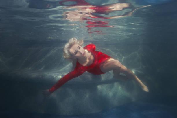 woman blonde under the water in the pool. - frau tiefer ausschnitt stock-fotos und bilder