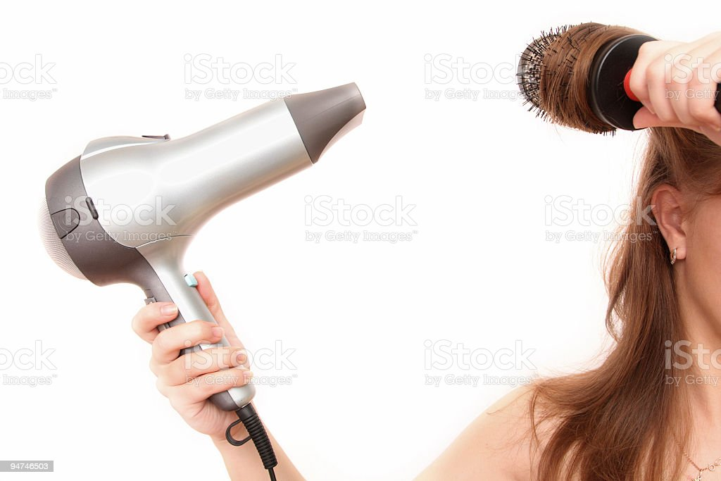 Woman blow drying her hair on white background stock photo