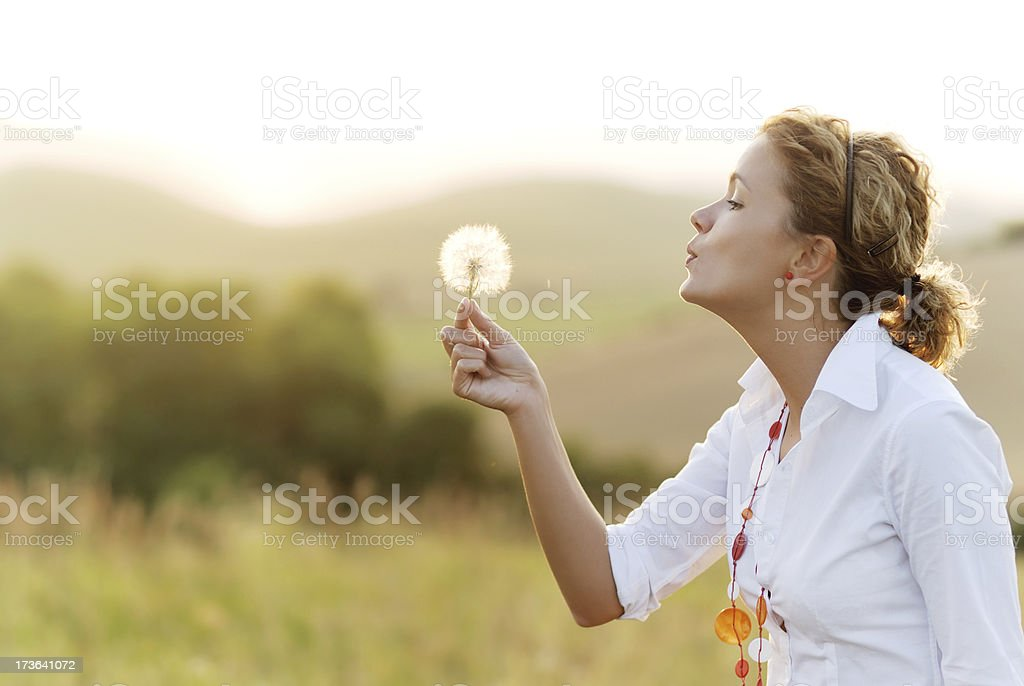 Woman blowing a dandelion in a field royalty-free stock photo