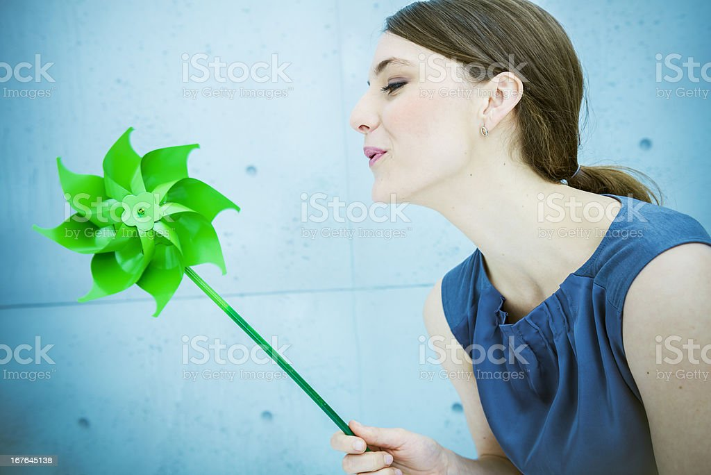 Woman blowing a pinwheel in nature royalty-free stock photo