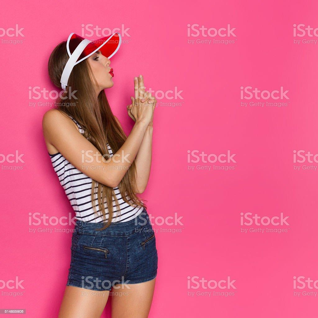 Woman Blowing At Finger Gun stock photo