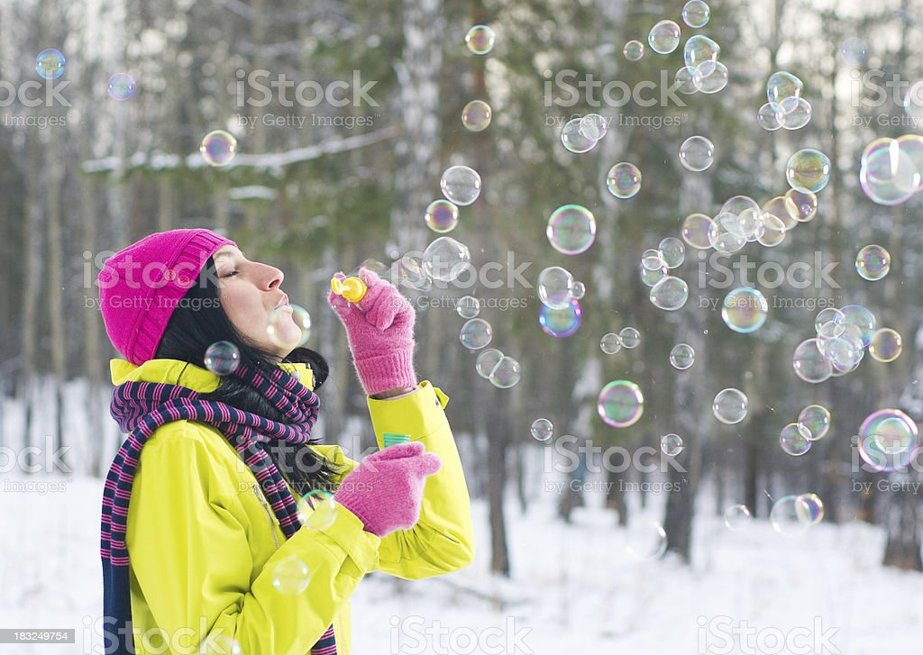 Woman blowing bubbles in winter forest royalty-free stock photo