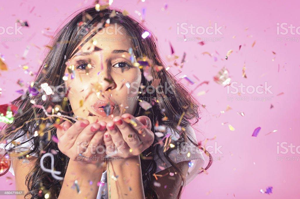 Woman blowing colourful confetti stock photo