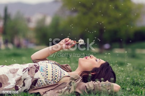 Young woman lying down in the grass and blowing a dandelion