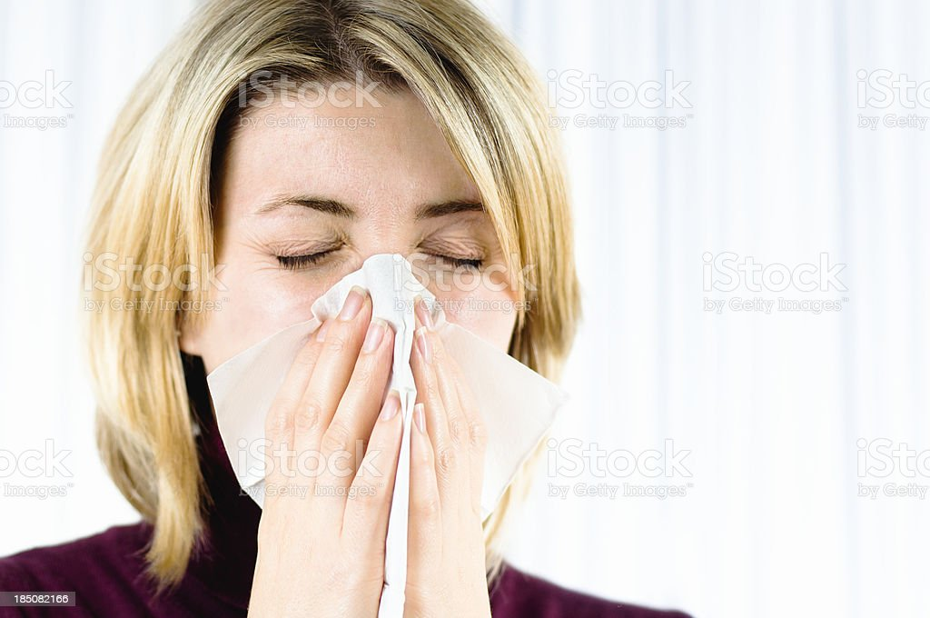 woman blowing her nose in the handkerchief stock photo