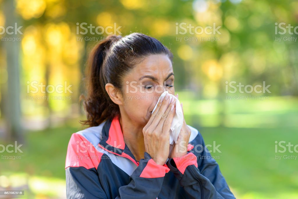 Woman blowing her nose on a tissue outdoors stock photo