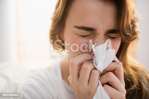 istock Woman blowing her nose on couch 665498060