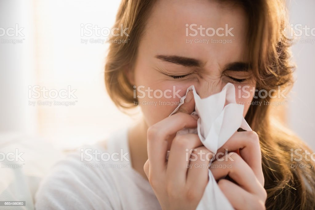 Woman blowing her nose on couch stock photo