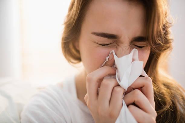 femme son moucher sur canapé - allergies photos et images de collection
