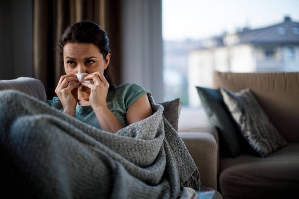 Woman blowing her nose Woman blowing her nose respiratory disease stock pictures, royalty-free photos & images