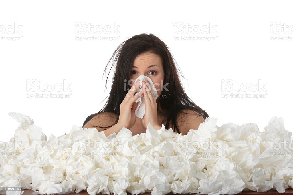 Woman blowing her nose with a huge pile of tissues in front stock photo