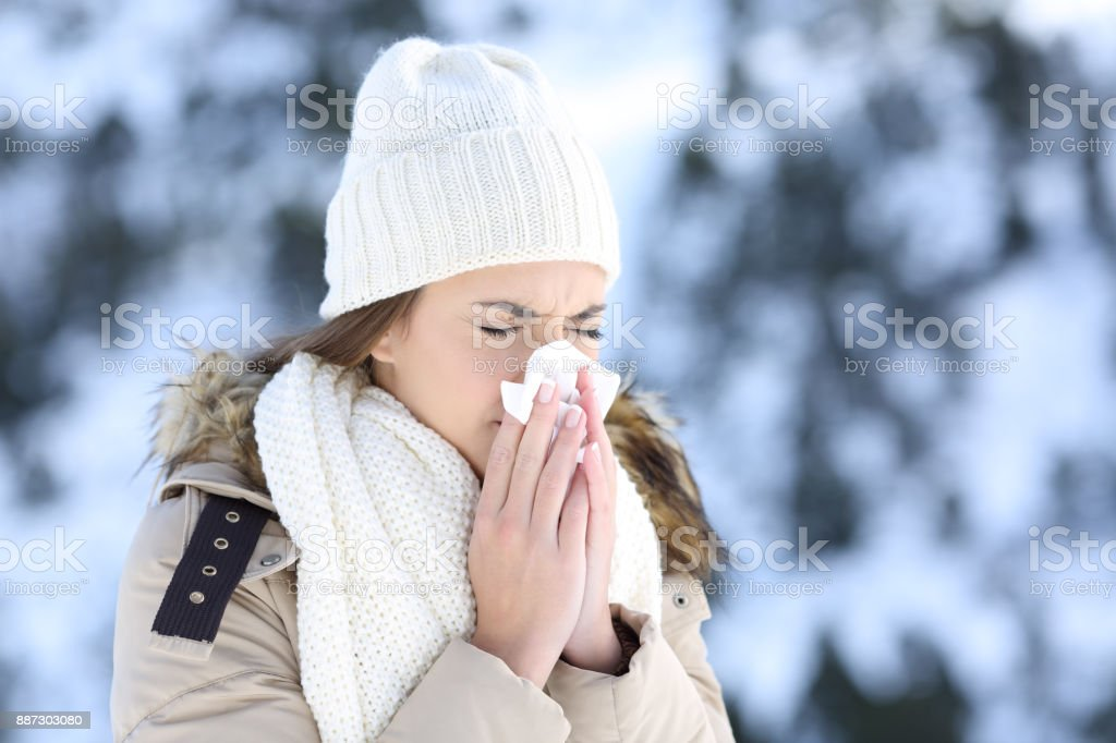 Woman blowing in a tissue in a cold snowy winter stock photo
