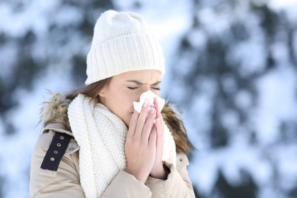 Woman blowing in a tissue in a cold snowy winter Woman blowing in a tissue in a cold winter with a snowy mountain in the background mucus stock pictures, royalty-free photos & images