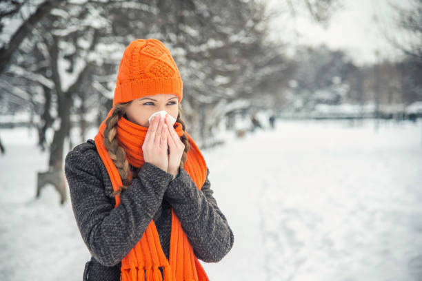 Woman blowing in a tissue in a cold snowy winter A young woman with braided long blond hair is outdoors in a park during the winter. There is snow and trees in the background. She is wearing winter clothes, an orange hat and scarf, and is blowing her nose with a handkerchief / hanky / tissue. She is looking away from the camera. With copy space. human parainfluenza virus stock pictures, royalty-free photos & images