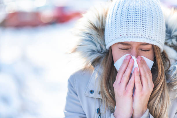 Woman blowing in a tissue in a cold winter with a snowy mountain in the background Woman blowing in a tissue in a cold winter with a snowy mountain in the background. There is nothing worse than winter illness. Winter illness concept with woman blowing into napkin outside in the snowy day mucus stock pictures, royalty-free photos & images