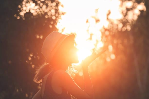 Frau bläst Kuss und hält Sonne in erzwungener Perspektive. – Foto