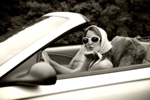 Woman Blowing Kisses From a Convertible