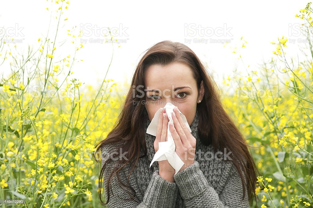 Woman blowing nose in a field of flowers stock photo