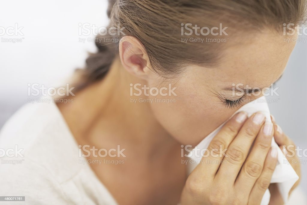 woman blowing nose into handkerchief stock photo