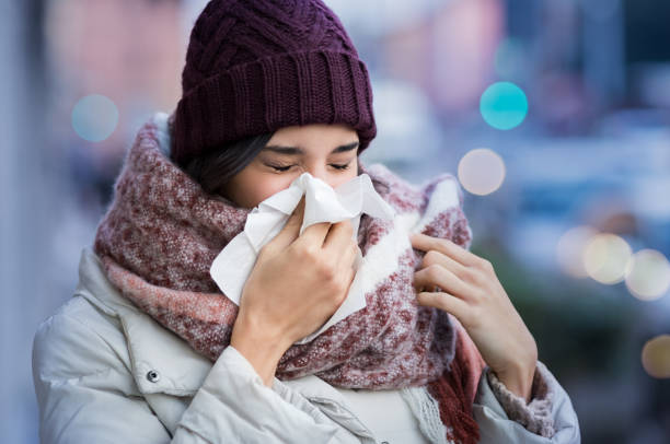 Woman blowing nose outdoor stock photo