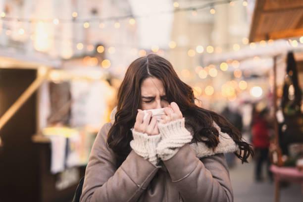kvinna blåser näsan stående på gatan på kallt väder. - cold street bildbanksfoton och bilder