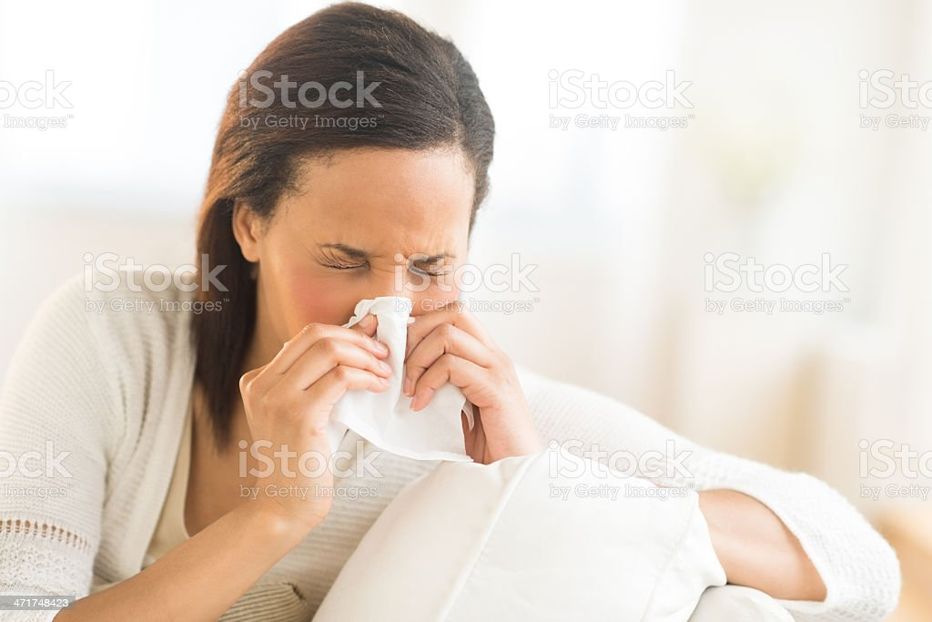 Woman Blowing Nose With Tissue At Home stock photo