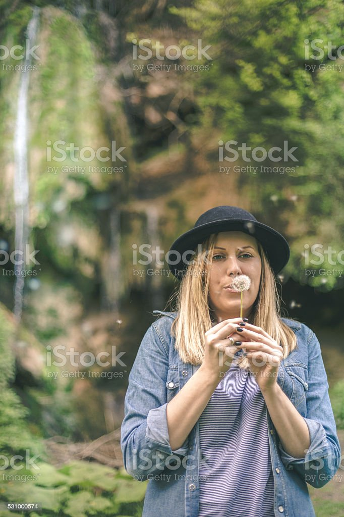 woman blowing on a dandelion muted colors vintage toned