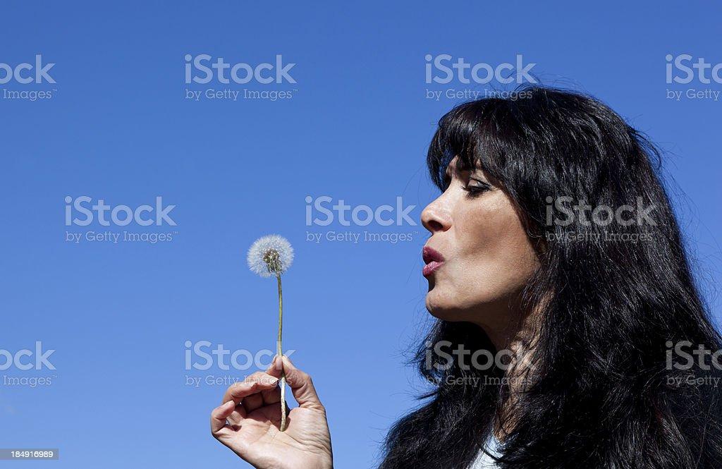 woman with black hair blowing on dandelion flower against blue sky