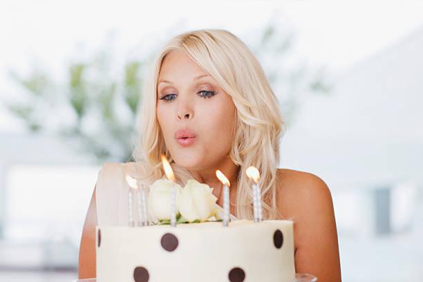 kobieta dmuchającego świeczki na tort urodzinowy, - 30 te urodziny zdjęcia i obrazy z banku zdjęć