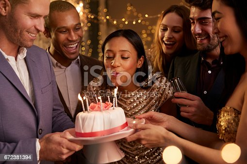 istock Woman Blowing Out Candles On Birthday Cake 672381394