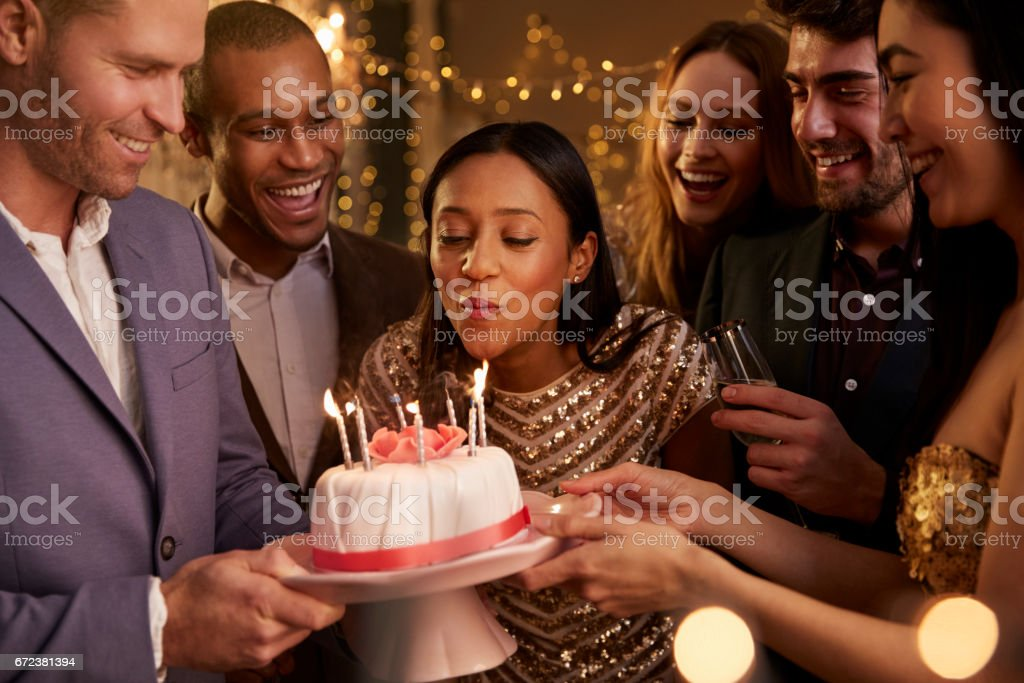 Woman Blowing Out Candles On Birthday Cake stock photo