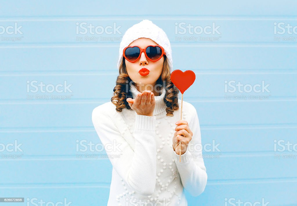 woman blowing red lips sends air kiss holds lollipop heart stock photo