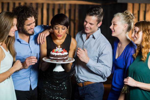 Woman blowing the candle on her birthday cake stock photo