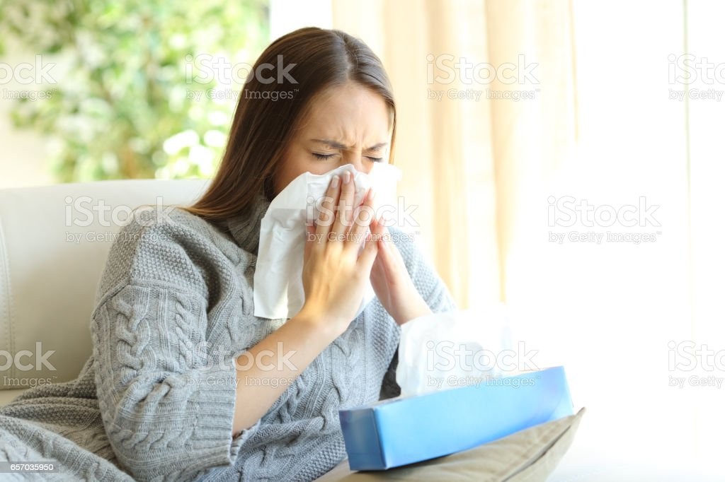 Woman blowing with flu in winter stock photo