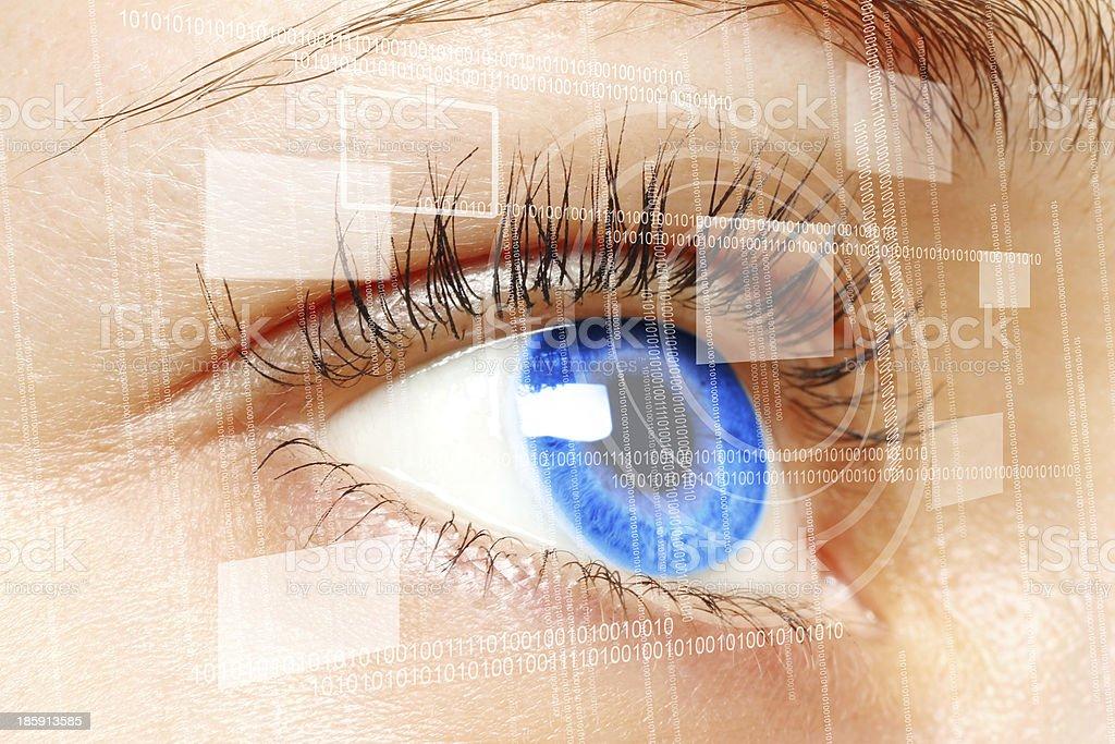 Woman blue eye looking at a digital virtual screen stock photo