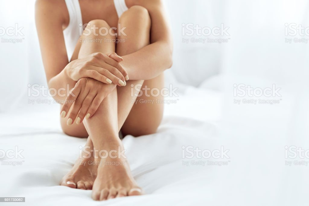 Woman Body Care. Close Up Of Long Legs With Soft Skin And Hands Woman Body Care. Close Up Of Long Female Legs With Perfect Smooth Soft Skin, Pedicure And Beautiful Hands With Natural Manicure, Healthy Nails On White Bed. Epilation, Beauty And Health Concepts Adult Stock Photo